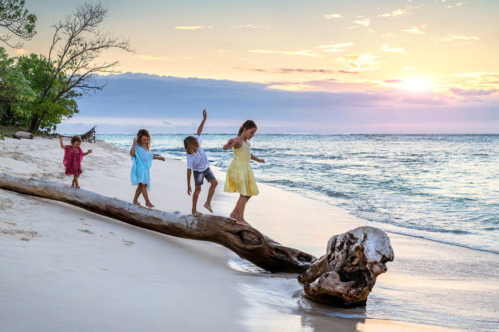 Children playing on beach at sunset