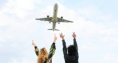 Two people waving to a plane flying above