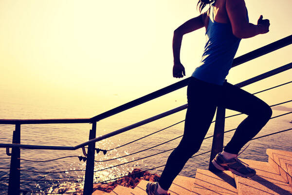 Woman running up stairs in fitness gear