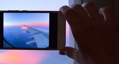 Man taking a picture through out of the plane window