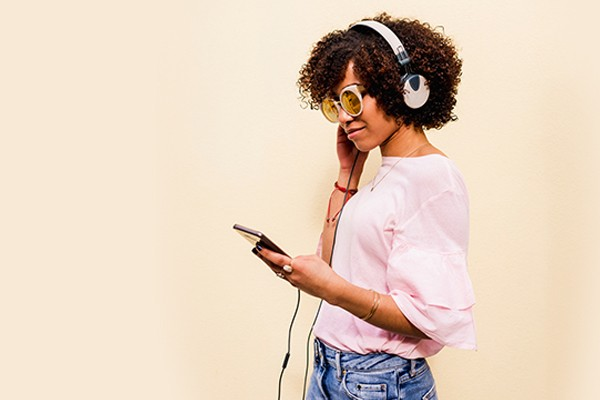 Image of person with headphones on looking at phone