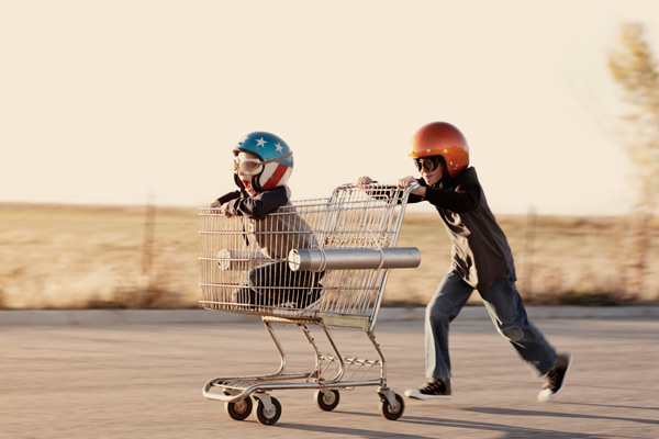 Kids playing with a shopping trolley