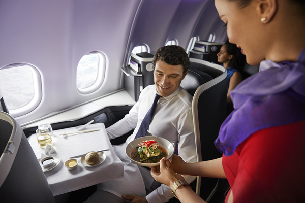 Man in business class enjoying is in flight meal