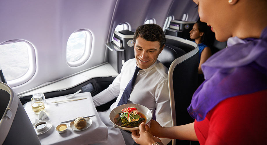 Female Virgin Australia cabin crew serving food to a man in The Business