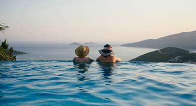Couple in pool looking out over mountains