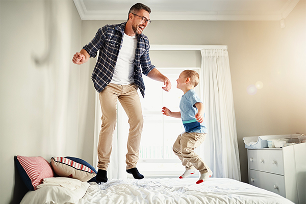 Father and son jumping on a bed